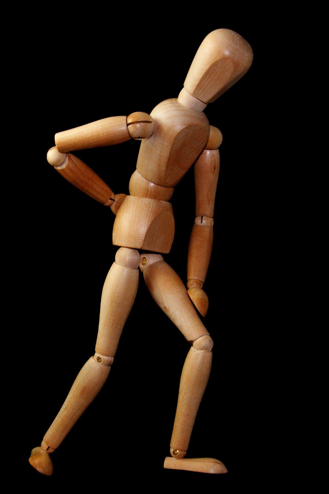 痛い腰をさする木製人形